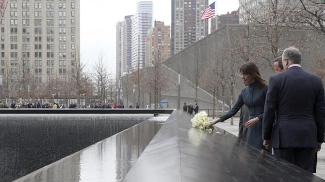 British Prime Minister David Cameron, center, and Charles Wolf, right, watch as Samantha Cameron places flowers in honor of Wolf's wife Katherine during a visit to the National September 11 Memorial, Thursday, March 15, 2012 in New York.  (AP Photo/Mary Altaffer, Pool)