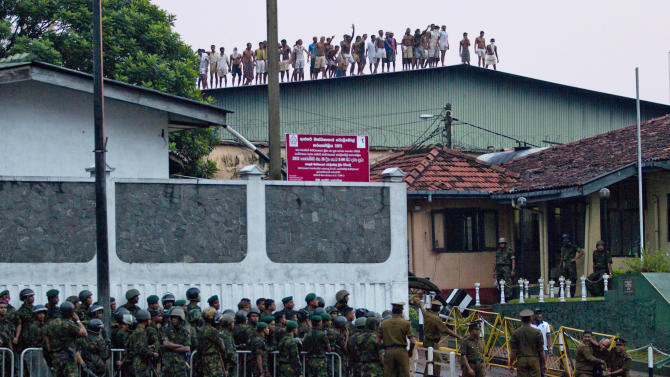 Sri Lankan inmates shout from a roof of a prison building as prison guards assist an injured colleague, foreground right, outside a prison in Colombo, Sri Lanka, Friday, Nov. 9, 2012. Sri Lankan security forces engaged in a gunbattle Friday night with rioting prisoners who appeared to have briefly taken control of at least part of a prison in Colombo. Officials said at least 13 people were wounded in the violence, with several dead. (AP Photo/Gemunu Amarasinghe)