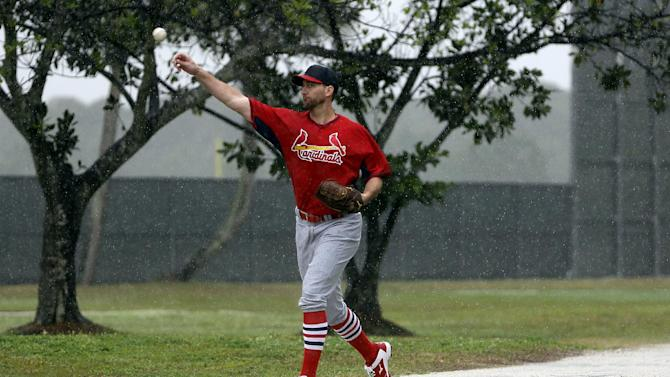 St. Louis Cardinals pitcher Adam Wainwright throws in a steady rain during spring training Friday, Feb. 27, 2015, in Jupiter, Fla. Rain forced the Cardinals indoors on Friday, but Wainwright played catch for a few minutes outside after missing two days of baseball practice due to an abdominal strain. (AP Photo/Jeff Roberson)