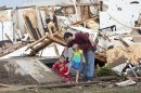 A man and two children walk through debris after a huge tornado struck Moore, Oklahoma