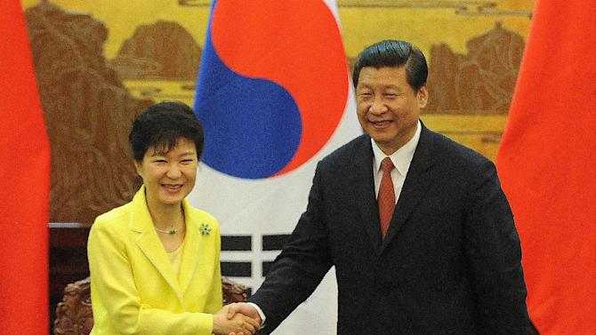 South Korean President Park Geun-Hye (left) shakes hands with her Chinese counterpart Xi Jinping after a ceremony at the Great Hall of the People in Beijing, on June 27, 2013