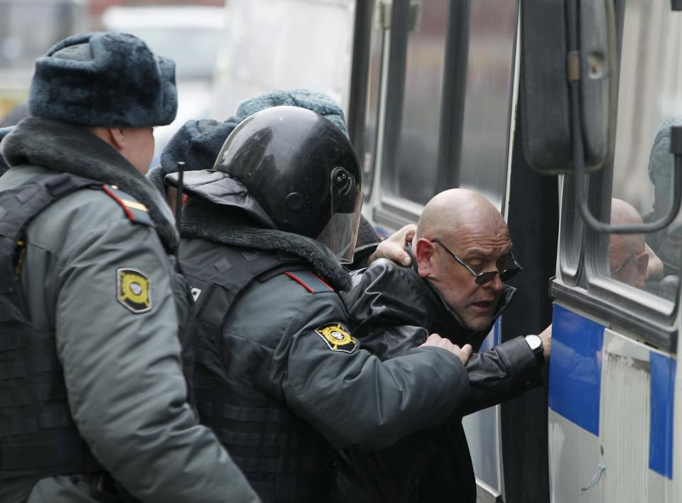 Police officers detain Russian opposition member outside the parliament building in downtown Moscow, Wednesday, April 11, 2012. Russia's Prime Minister Vladimir Putin is to speak at Parliament on Wednesday in his first major public speech since his victory in the March 4 presidential election. (AP Photo/Misha Japaridze)