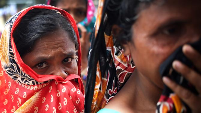 Women cover their noses as they watch people identify bodies at a school turned make-shift morgue where family members come to identify and claim bodies found in the garment factory building collapse, Thursday, May 2, 2013, in Savar, near Dhaka, Bangladesh. Rescuers found more bodies in the concrete debris of the collapsed garment factory building Thursday and authorities said it may take another five days to clear the rubble. In addition to the 430 confirmed dead, police report another 149 people are still missing in what has become the worst disaster for Bangladesh's $20 billion-a-year garment industry that supplies global retailers.(AP Photo/Wong Maye-E)