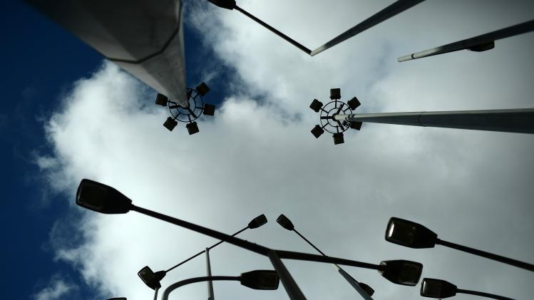 Street lights are silhouetted against the sky in Bilbao
