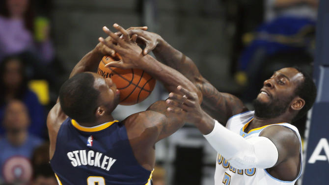 Indiana Pacers guard Rodney Stuckey, left, is stopped as he drives for a shot by Denver Nuggets forward J.J. Hickson in the first quarter of an NBA basketball game Saturday, Dec. 20, 2014, in Denver. (AP Photo/David Zalubowski)