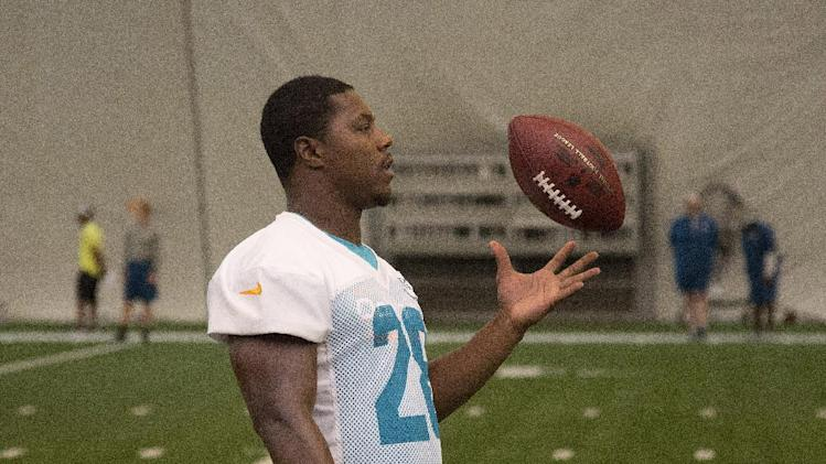 Miami Dolphins' Knowshon Moreno plays with a football during NFL football training camp Friday, July 25, 2014, in Davie, Fla. (AP Photo)