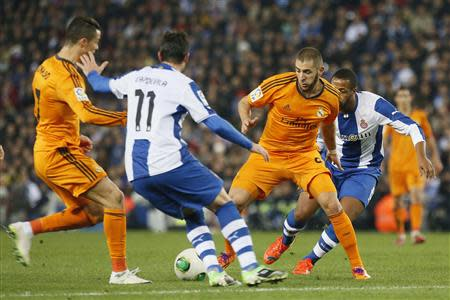 Real Madrid's Cristiano Ronaldo and Karim Benzema battle for the balll against Espanyol's Joan Capdevila and Sidnei Rechel during their King's Cup soccer match at Cornella El Prat stadium,