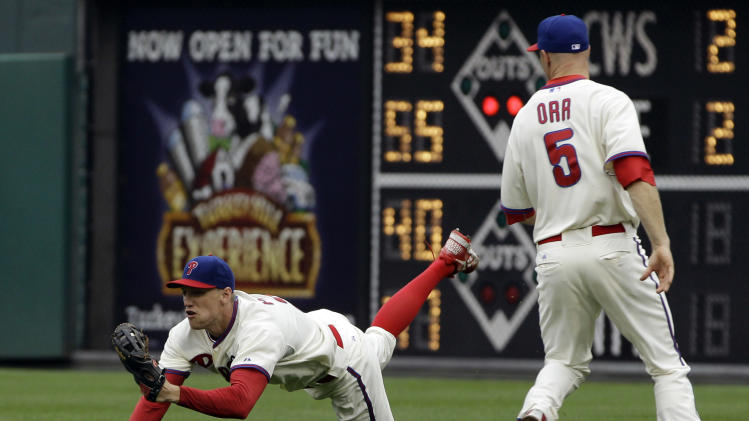 Philadelphia Phillies right fielder Hunter Pence, left, catches a fly out by Washington Nationals' Laynce Nix as second baseman Pete Orr looks on in the fourth inning of a baseball game, Tuesday, Sept. 20, 2011, in Philadelphia. (AP Photo/Matt Slocum)