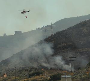A fire attack helicopter flies over with water as crews work to fight a fire burning near Rockport reservoir, near Wanship, Utah, Tuesday, Aug. 13, 2013. (AP Photo/Deseret News, Scott G Winteton)