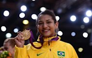 Brazil&#39;s Sarah Menezes poses on the podium with her gold medal at the London 2012 Olympics on July 28. Menezes revealed Sunday that her parents tried to stop her from taking up the sport which they believed was for men only. The 22-year-old from Brazil became the first woman from her country to win an Olympic judo gold