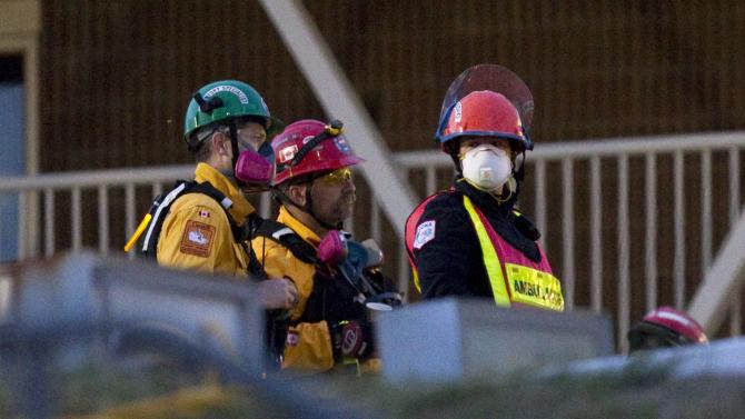 Rescue workers wait to access the wreckage of the Algo Centre Mall in Elliot Lake, Ontario, Canada on Wednesday, June 27, 2012.  Officials recovered a body Wednesday after spending the night dismantling a partially collapsed Ontario mall in a renewed rescue effort after angry residents had shouted down fears that the unstable structure made the work too risky to continue.  Part of the roof collapsed last Saturday afternoon. At least 22 people had minor injuries.  (AP Photo/The Canadian Press, Chris Young)