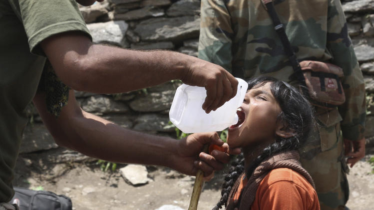 In this Friday, June 21, 2013 photo, an Indian army soldier helps a young girl, affected by floods, drink water before evacuating her from the upper reaches of mountains, in Gaurikund, in northern Indian state of Uttrakhand. Officials say soldiers are working to evacuate tens of thousands of people still stranded in northern India where nearly 600 people have been killed in monsoon flooding and landslides. (AP Photo)
