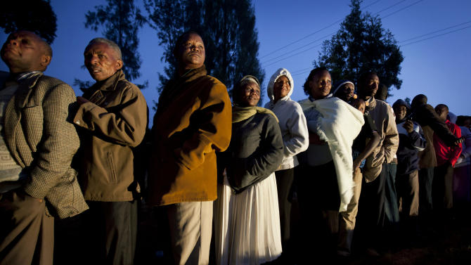 Kenyans line up to cast their vote in the early morning at the Mutomo primary school near Gatundu, north of Nairobi, in Kenya Monday, March 4, 2013. Five years after more than 1,000 people were killed in election-related violence, Kenyans went to the polls on Monday to begin casting votes in a nationwide election seen as the country's most important - and complicated - in its 50-year history. (AP Photo/Ben Curtis)