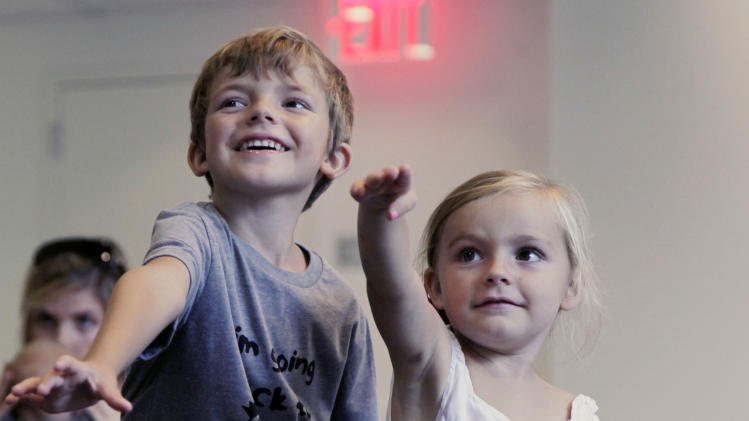 "In this Sept. 5, 2012, photo, from left, Aidan Lain, 7, and Zoe Shyba, 3, play ""Kinect Sesame Street TV"" at the Sesame Street Workshop  in New York. ""Kinect Sesame Street TV"",  launching Tuesday,  Sept. 18, 2012, uses Kinect, a motion and voice-sensing controller created by Microsoft, to give Elmo, Big Bird and the rest of the Sesame Street crew a chance to have a real two-way conversation with their pint-sized audience. The effort represents the next step in the evolution of television, adding an interactive element to what's still largely a passive, lean-back experience. (AP Photo/Mark Lennihan)"