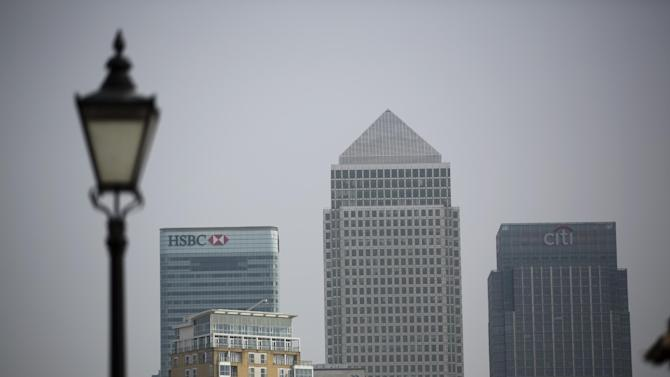 """A Victorian era styled street lamp stands in the foreground as an exterior views shows the global headquarters building of HSBC, at left, next to the pyramid roof topped building """"One Canada Square"""" and the Citigroup Centre building, right, in the Canary Wharf business district of London, Friday, April 24, 2015. HSBC is considering moving its headquarters from Britain in the wake of """"regulatory and structural reforms"""" imposed after the 2008 financial crisis, the bank's chairman said Friday. (AP Photo/Matt Dunham)"""