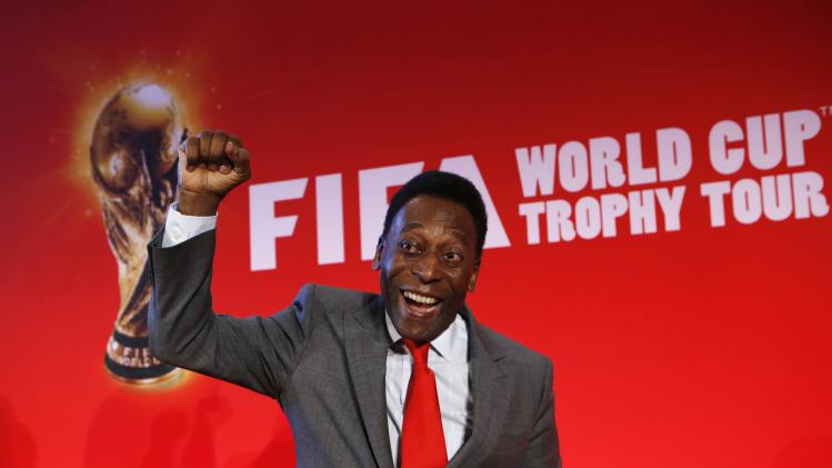 "Brazilian soccer legend Pele reacts as he poses after a news conference to present the FiFA World Cup global ""Trophy Tour"" in Paris"