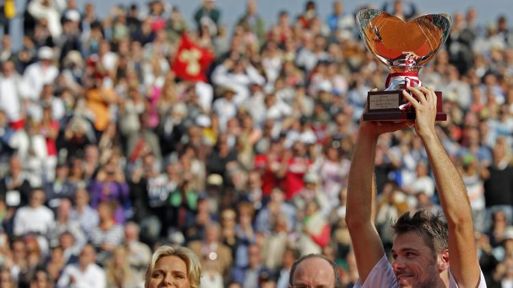 Wawrinka of Switzerland holds up his trophy while Princess Charlene and Prince Albert II of Monaco look on, after winning the final match against compatriot Federer at the Monte Carlo Masters in Monaco