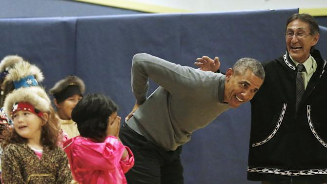 Obama jokingly pretends to hurt his back as he dances with children performing a traditional Yup'ik dance at a school in Dillingham