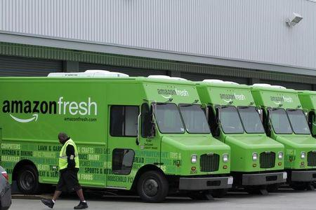 A worker walks past Amazon Fresh delivery vans parked at an Amazon Fresh warehouse in Inglewood
