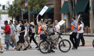 Tampa, Fla., police officers on bicycles watch demonstrators as they cross the street to attend a rally Sunday, Aug. 26, 2012, in Tampa, Fla. Hundreds of protestors gathered in Gas Light Park in downtown Tampa to march in demonstration against the Republican National Convention. (AP Photo/Dave Martin)