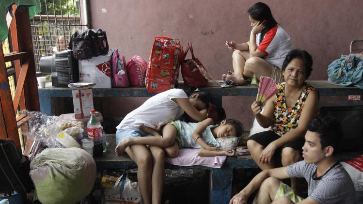 A Filipino family stays inside a temporary evacuation center after fire hit their homes at a slum area in suburban San Juan, east of Manila, Philippines on Christmas day Tuesday Dec. 25, 2012. Fire Officer 2 Noel Binwag said about 2,000 families were left homeless during the fire. Six people also died when a row of apartments went up in flames in a separate fire in suburan Quezon city. (AP Photo/Aaron Favila)