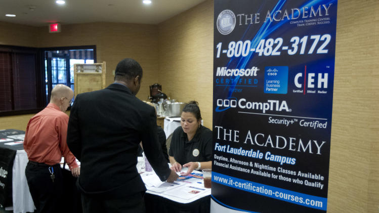 In this Friday, Nov. 30, 2012, photo, an unidentified job seeker talks to recruiters from a trade school at the Fort Lauderdale Career Fair, in Dania Beach, Fla. Weekly U.S. unemployment benefit applications fell 25,000 last week to a seasonally adjusted 370,000, the government said Thursday. The third straight drop shows a temporary spike caused by Superstorm Sandy has faded. (AP Photo/J Pat Carter)