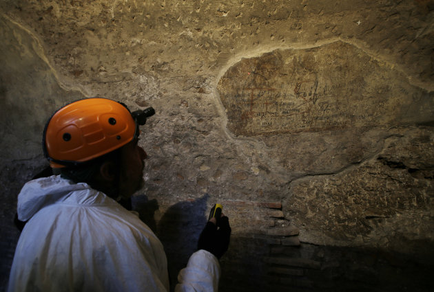 A restorer shows journalists an ancient graffiti recently discovered inside a gallery of Rome's Colosseum, Friday, Jan. 18, 2013. A long-delayed restoration of the Colosseum's only intact internal pas