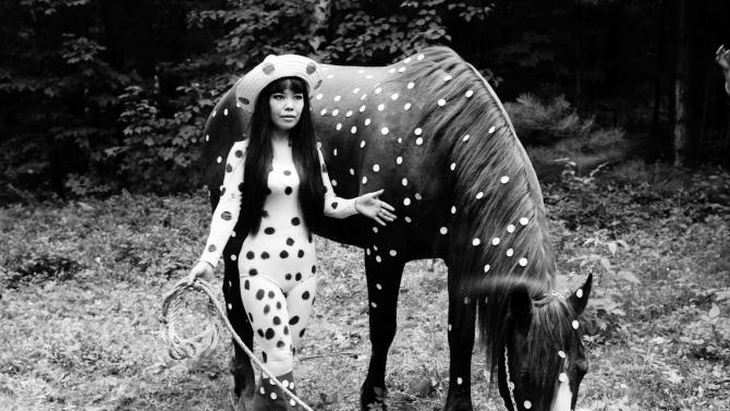 """In this 1967 photo released by Yayoi Kusama Studio Inc., Japanese artist Yayoi Kusama poses with a horse in a happening titled """"Horse Play"""" in Woodstock, New York. Kusama's signature splash of dots has now arrived in the realm of fashion in a new collection from French luxury brand Louis Vuitton - bags, sunglasses, shoes and coats. The latest Kusama collection is showcased at its boutiques around the world, including New York, Paris, Tokyo and Singapore, sometimes with replica dolls of Kusama. (AP Photo/Yayoi Kusama Studio Inc.) NO SALES, EDITORIAL USE ONLY, CREDIT MANDATORY"""