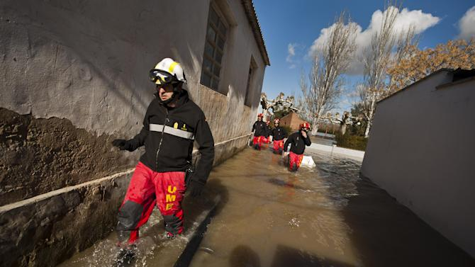 Members of Militar Emergency Unit, patrol a street near to Ebro River in the small town of Novillas, northern Spain, Friday, Feb. 27, 2015. Heavy rain has lead to flooding in northern Spain over the past few days, especially in Navarra provinces and Aragon.(AP Photo/Alvaro Barrientos)