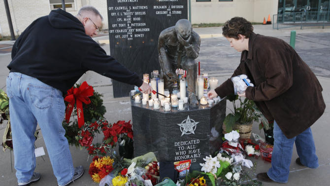 Topeka Police Lt. Jack Mackey, left, and Jennifer Walker light candles in honor of two officers killed in the line of duty in Topeka, Kan., Monday, Dec. 17, 2012. A man with a history of theft and weapons convictions gunned down two police officers investigating possible drug activity in a Kansas grocery parking lot, and was later killed after an armed standoff, authorities said Monday. (AP Photo/Orlin Wagner)