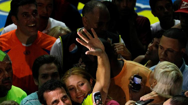Opposition presidential candidate Henrique Capriles waves to supporters as he speaks with the media after playing a basketball game with friends in Caracas, Venezuela, Friday, April 12, 2013. Capriles is running against ruling party candidate Nicolas Maduro in the April 14 presidential election. (AP Photo/Fernando Llano