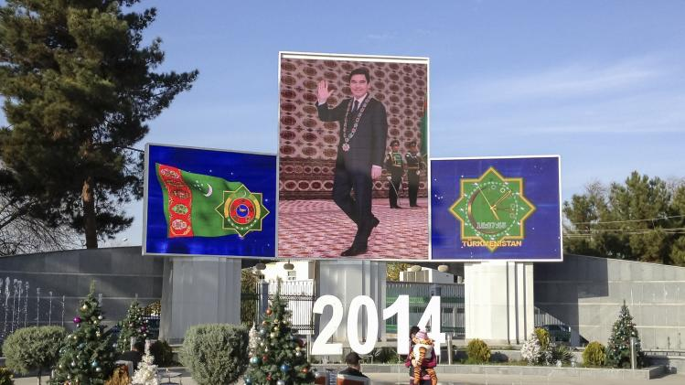 People rest in front of screens showing Turkmenistan's President Berdymukhamedov and the national symbols in Ashgabat