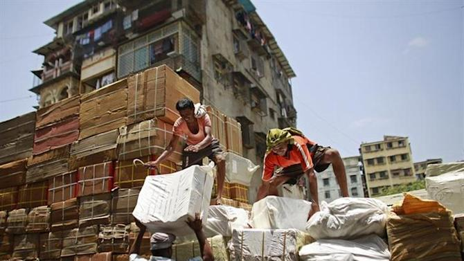 Workers of a transport company load packages on a truck at a wholesale market in Mumbai May 13, 2013. REUTERS/Danish Siddiqui/Files