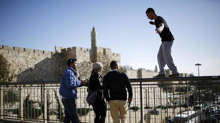 People watch as a Palestinian practices parkour outside Jerusalem's Old City