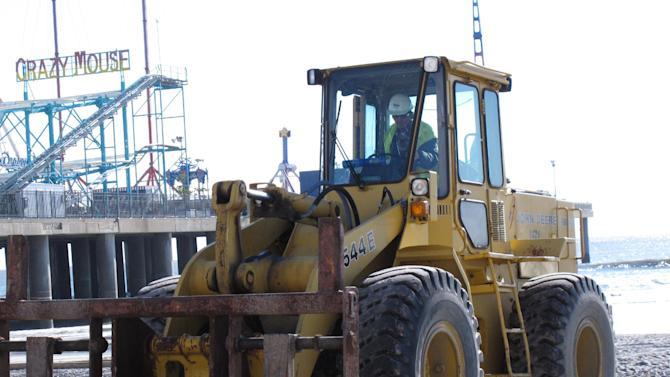 A worker uses heavy machinery to lift wooden pilings on the Atlantic City NJ Boardwalk on Wednesday, Nov. 14, 2012, as part of the Margaritaville entertainment complex. Construction began Wednesday on the $35 million Jimmy Buffett-themed project at Resorts Casino Hotel. (AP Photo/Wayne Parry)