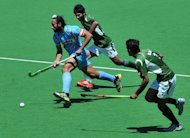 Captain Sadar Singh of India (left) runs through Muhammad Waqas and Haseem Abdul Khan of Pakistan during the bronze medal match at the men&#39;s Hockey Champions Trophy tournament in Melbourne. Australia went some way to erasing the pain of their London Olympics flop by winning a record fifth consecutive Champions Trophy in a 2-1 extra-time victory over the Netherlands