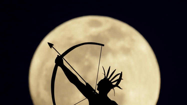 AP10ThingsToSee - A full moon rises behind a statue of a Kansas Indian on top of the Kansas Statehouse Wednesday, April 24, 2013, in Topeka, Kan. (AP Photo/Charlie Riedel, File)