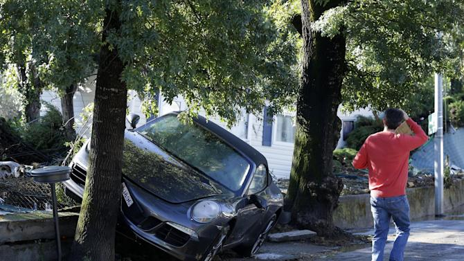 A man walks past a damaged car in Biot, near Cannes, southeastern France, Sunday Oct.4, 2015. Sudden heavy rains around the French Riviera have killed at least 10 people, including some trapped in cars, a campsite and a retirement home, and left six missing. Car and train traffic was disrupted along the Mediterranean coast. (AP Photo/Lionel Cironneau)