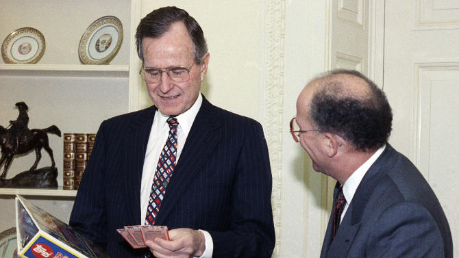 FILE - In this Feb. 5, 1990 file photo, President George H.W. Bush jokes with Arthur Shorin, President of Topps, Co., Inc., after Shorin presented him a book of baseball cards during a meeting in the Oval Office in Washington. Baseball cards depicting the former president as a Yale first baseman have fetched thousands of dollars each since they were specially-made for the White House in 1990. But Joe Orlando, president of Professional Sports Authenticator in Santa Ana, Calif., said Tuesday, July 9, 2013, thatmany of the Bush cards in circulation were not part of the set presented to the president. ( AP Photo/Dennis Cook, File)