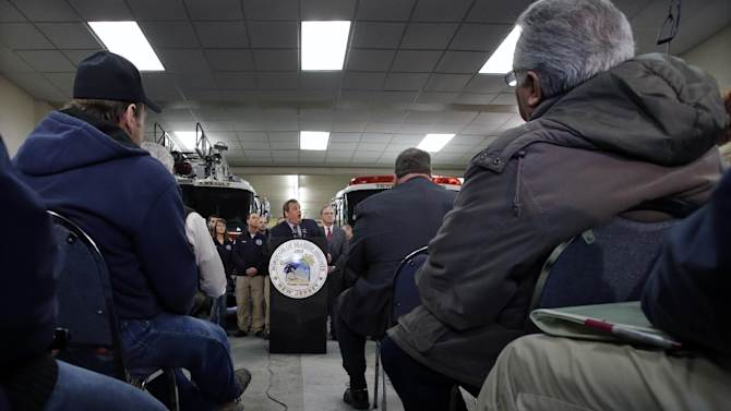 """Seaside Heights residents listen as New Jersey Gov. Chris Christie, center, announce his """"Hurricane Sandy Flood Map Regulations"""" Thursday, Jan. 24, 2013, in Seaside Heights, N.J. The town, which was featured in the MTV reality show """"Jersey Shore"""" sustained substantial damage to homes and its boardwalk during Superstorm Sandy. The guidelines will include where and how high to rebuild. (AP Photo/Mel Evans)"""