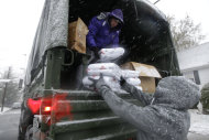 Volunteers Chris Braitsch, left, Karina Ayubi unload blankets donated by the American Red Cross as a Nor'easter approaches in the wake of Superstorm Sandy, Wednesday, Nov. 7, 2012, in Little Ferry, N.J., a town that was flooded during the storm and where some residents were still without power. (AP Photo/Kathy Willens)