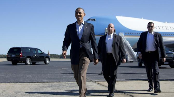 President Barack Obama walks to greet people on the tarmac as he arrives at Newport News Williamsburg International Airport on Air Force One, Saturday, Oct. 13, 2012, in Williamsburg, Va. (AP Photo/Carolyn Kaster)