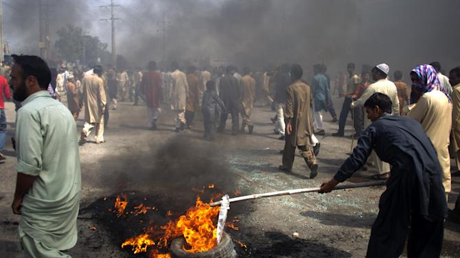 Pakistani protesters burn tires to block the main highway in Rawalpindi, Pakistan on Friday, Sept. 21, 2012. Pakistan has blocked cell phone service in major cities to prevent militants from using phones to detonate bombs during a national day of protest against an anti-Islam film produced in the United States. (AP Photo/B.K. Bangash)
