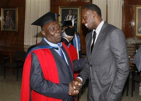 Jamaican sprinter Bolt congratulates his coach Mills after Mills received degree of Doctor Honoris Causa from University of the West Indies in Mona