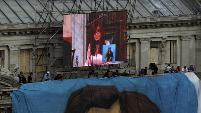Argentina's President Fernandez de Kirchner is seen on a large television screen placed outside the Argentine Congress above a large image of her during her speech to lawmakers at the opening session of the 133rd legislative term of Congress in Buenos