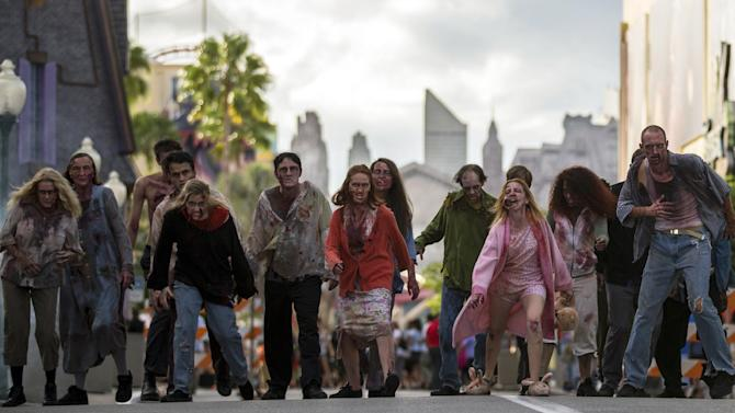 """This September 2013 image provided by Universal Orlando in Orlando, Fla., shows actors portraying zombies for the theme park's Halloween Horror Nights, which take place on select nights through Nov. 2. The zombies are inspired by AMC's show """"The Walking Dead."""" One of the park's eight haunted houses is also themed on the show. (AP Photo/Universal Orlando)"""
