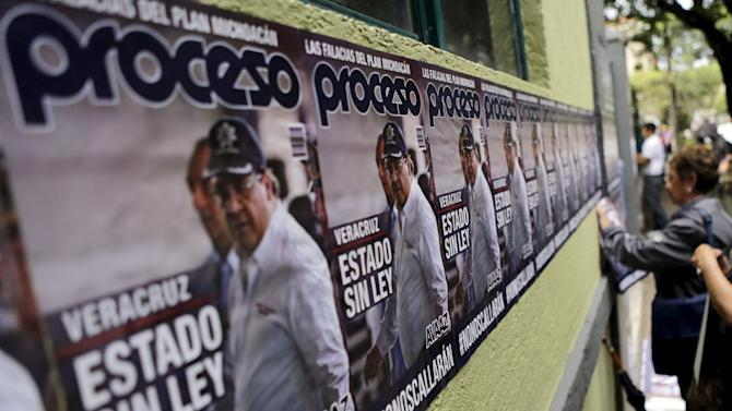 Activists put up posters with an image of Veracruz state governor Duarte during a demonstration against the murder of photojournalist Espinosa and four women, outside the Government of Veracruz building in Mexico City