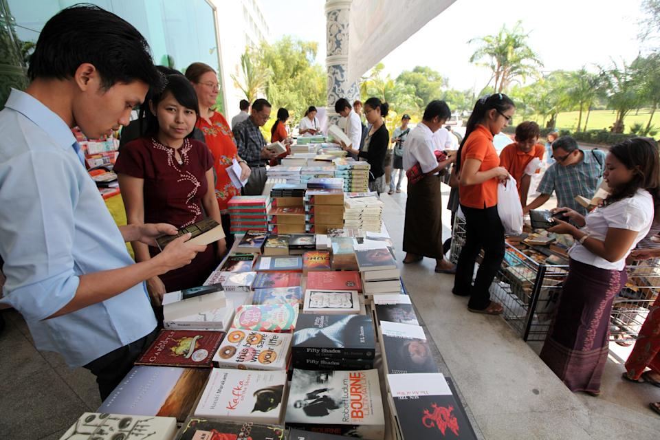 Visitors buy books displayed during the Irrawaddy Literary Festival at Inya Lake hotel Friday, Feb. 1, 2013, in Yangon, Myanmar. The country's first international literary festival opens Friday, featuring dozens of authors from around the world, including Nobel Peace Prize laureate Aung San Suu Kyi. (AP Photo/Khin Maung Win)