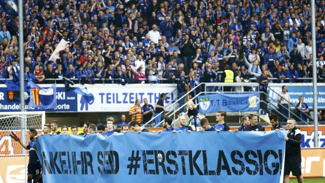 SC Paderborn players hold a banner after loosing to VFB Stuttgart during their German Bundesliga first division soccer match in Paderborn