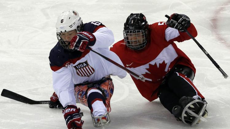 Canada's Rempel fights for the puck with Farmer of the U.S during the semi-final sledge hockey game at the 2014 Sochi Winter Paralympic Games